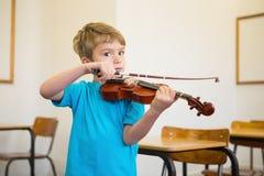 Allievo sveglio che gioca violino in aula Immagini Stock