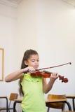 Allievo sveglio che gioca violino in aula Immagini Stock Libere da Diritti