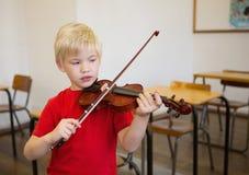 Allievo sveglio che gioca violino in aula Immagine Stock