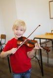 Allievo sveglio che gioca violino in aula Immagine Stock Libera da Diritti