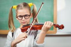 Allievo sveglio che gioca violino in un'aula Immagine Stock