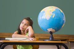 Allievo sveglio che pensa nell'aula con il globo Fotografie Stock