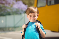 Allievo sveglio che sorride alla macchina fotografica in scuolabus Immagine Stock