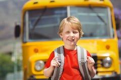 Allievo sveglio che sorride alla macchina fotografica in scuolabus Immagini Stock