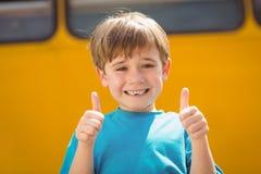 Allievo sveglio che sorride alla macchina fotografica in scuolabus Fotografia Stock