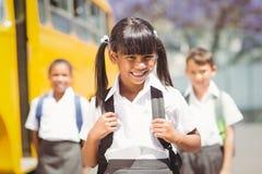 Allievo sveglio che sorride alla macchina fotografica in scuolabus Fotografia Stock Libera da Diritti