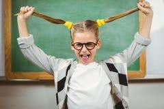 Allievo sveglio che tira i suoi capelli in un'aula Fotografia Stock