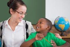 Allievo sveglio ed insegnante che sorridono ad a vicenda in aula Immagine Stock Libera da Diritti