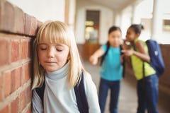 Allievo triste che è oppresso dai compagni di classe al corridoio Fotografia Stock