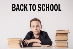 Allievo in vestito al suo scrittorio su fondo grigio con i libri ` dell'iscrizione di nuovo al ` della scuola Fotografia Stock Libera da Diritti