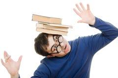 Allievo in vetri con un libro sulla sua testa Immagine Stock