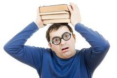 Allievo in vetri con un libro sulla sua testa Immagini Stock