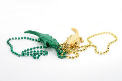 Alligator beads. Green and gold Mardi gras beaded necklaces with alligators on white background Royalty Free Stock Image