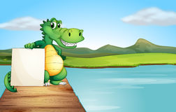 An alligator holding an empty board at the wooden bridge Royalty Free Stock Photos