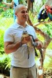 Alligatore del bambino della tenuta del giovane, isola della giungla, Miami, 2014 Fotografie Stock Libere da Diritti