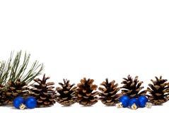 Allineamento del cono del pino e piccoli ornamenti blu Immagini Stock Libere da Diritti