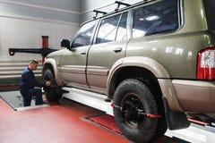 Allineamento di ruota per SUV in officina professionale Fotografia Stock Libera da Diritti