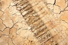 Allineamento di ruota sui dettagli della terra le crepe nel suolo Fotografie Stock
