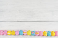 Allineamento sveglio dell'uovo di Pasqua su bianco rustico o su Gray Wood Boards per fondo con spazio o stanza per testo, copia,  Immagine Stock