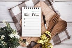 Allini il blocco note con il testo della lista di piano di dieta sul tagliere con il wo Fotografia Stock