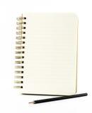 Allini il taccuino di carta con la matita nera isolata sul backgrou bianco Fotografia Stock