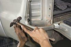 Allini l'automobile del corpo del metallo con il martello Immagini Stock