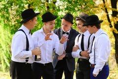 Allini realmente gli amici parlano di qualcosa e dimostrano Gruppo di uomini che parlano all'aperto in buon tempo Communicatio de Fotografie Stock Libere da Diritti