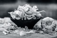 Allium sativum, aglio crudo in una ciotola dell'argilla su un fondo dell'iuta Fotografie Stock