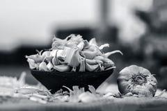 Allium sativum, aglio crudo in una ciotola dell'argilla su un fondo dell'iuta Immagini Stock Libere da Diritti