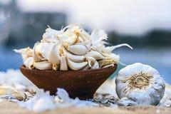 Allium sativum, aglio crudo in una ciotola dell'argilla su un fondo dell'iuta Fotografie Stock Libere da Diritti
