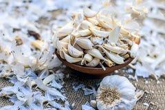 Allium sativum, aglio crudo in una ciotola dell'argilla su un fondo dell'iuta Immagini Stock
