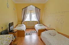 Allmän sikt av en inre av det trefaldiga hotellrummet med en inskrift på en vägg Arkivfoto