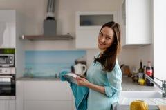 Allmän stående av en ung flicka i inre av ett ljust kök med en handduk och en platta i hans händer Verkliga livet Royaltyfri Fotografi