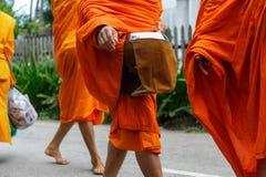 Allmosa för buddistiska munkar mot efterkrav i Luang Prabang, Laos royaltyfri bild