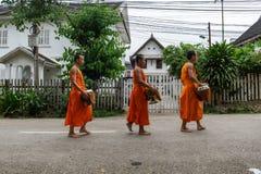 Allmosa för buddistiska munkar för novis mot efterkrav i Luang Prabang, Laos arkivfoto
