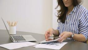 Allo scrittorio la donna stampa rapidamente sul computer portatile quindi esamina la compressa stock footage