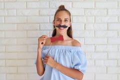 Allo stesso tempo baffi piacevoli seri della carta della tenuta della ragazza Fotografie Stock