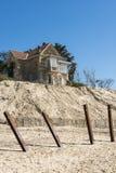 Alloggi con erosione dei pali alla spiaggia Fotografia Stock