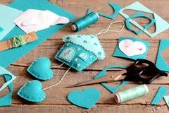 Alloggi con la decorazione dei cuori fatta da feltro, dagli strumenti e dai materiali per il cucito, modelli di carta sulla vecch Fotografie Stock
