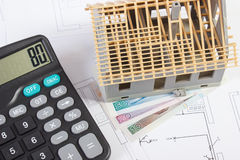 Alloggi in costruzione, calcolatore e lucidi la valuta sui disegni elettrici, concetto della casa della costruzione Fotografia Stock