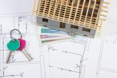 Alloggi in costruzione, chiavi e lucidi la valuta sui disegni elettrici, concetto della casa della costruzione Fotografia Stock Libera da Diritti
