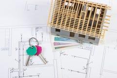 Alloggi in costruzione, chiavi e lucidi la valuta sui disegni elettrici, concetto della casa della costruzione Immagine Stock Libera da Diritti