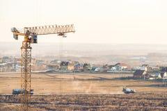 Alloggi in costruzione con una gru a torre e due camion su fondo Fotografia Stock Libera da Diritti