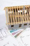 Alloggi in costruzione e lucidi la valuta sui disegni elettrici, concetto della casa della costruzione Fotografia Stock Libera da Diritti