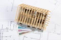 Alloggi in costruzione e lucidi la valuta sui disegni elettrici, concetto della casa della costruzione Fotografie Stock Libere da Diritti