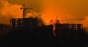 Alloggi in costruzione nell'evaporazione nebbiosa al tramonto, fondo Fotografia Stock Libera da Diritti