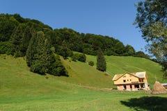 Alloggi in costruzione nelle colline verdi coperte di foresta verde e di chiaro cielo blu Fotografia Stock
