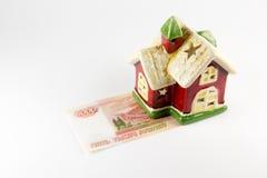 Alloggi e cinque mila rubli di soldi su un fondo bianco Fotografia Stock Libera da Diritti