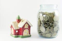 Alloggi e un barattolo di vetro con le monete su un fondo bianco Immagini Stock