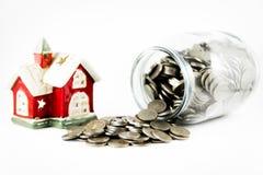 Alloggi e un barattolo di vetro con le monete su un fondo bianco Immagine Stock